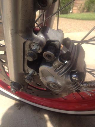 Coloque la pinza sobre el rotor y alinear los dos agujeros con el control deslizante tenedor utilizan el wrech 10 mm para apretar la pinza en su lugar. Una vez instalada la pinza. Bombear el freno delantero para conseguir todo el aire