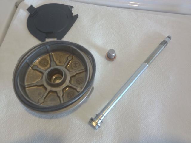 Limpie la carcasa del filtro de aceite. Retire la tapa de la carcasa del filtro de aceite (tapa de plata redonda justo a la derecha de la parte delantera del motor) con toma de 13 mm girando la llave en sentido antihorario.