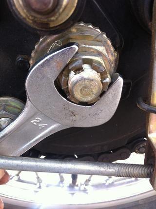 Utilice una llave de 24 mm para retirar la primera tuerca. Gire contra las agujas del reloj para eliminar esta tuerca. Esta es la tuerca que sujeta el perno que posee la totalidad de la rueda trasera.