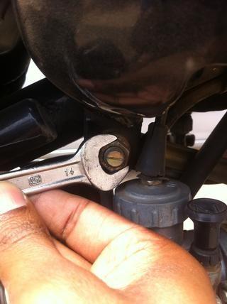Aflojando la tuerca trasera con una llave de 14 mm mientras se mantiene el perno con una llave inglesa mismo tamaño en el otro lado.