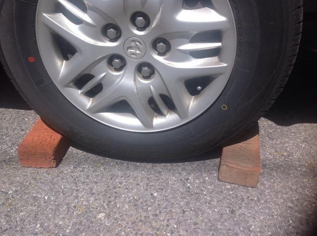 Coloque las piezas de madera / grandes bloques hasta apretados contra el frente y la parte posterior de la llanta que está en diagonal a través de ser cambiado por una. Esto eliminará las posibles posibilidades de que el balanceo del coche.