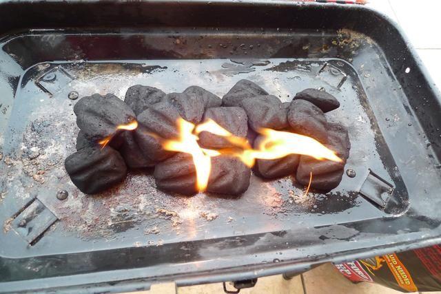 Encienda las briquetas de carbón. Se tarda unos 15 minutos para que el turno de carbón para el carbón y el resplandor rojo.