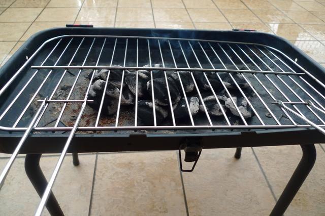 Coloque una rejilla de la parrilla sobre el carbón caliente.