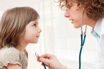niño siendo examinado por médico