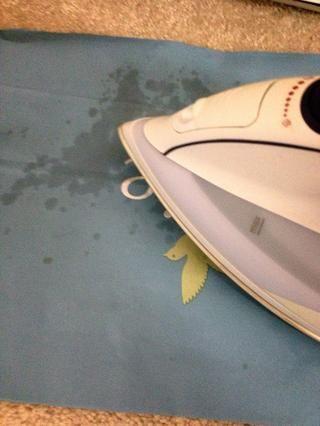 Comience a planchar sobre ella, utilizando el calor directo para derretir la cera de la alfombra en el papel! El papel absorbe la cera muy bien. Después de utilizar una tira, colocarlo en su toalla de mano.