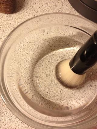 Tome un cepillo y lo puso en uno de los cuencos con agua caliente.