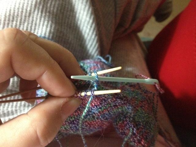 Ahora tome la aguja, de nuevo purlwise, a través de la primera puntada en la aguja de nuevo. Tire del hilo a través de - de nuevo, no demasiado fuerte.