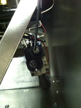 Con un destornillador de punta plana aflojar el tornillo de sujeción de plástico interior