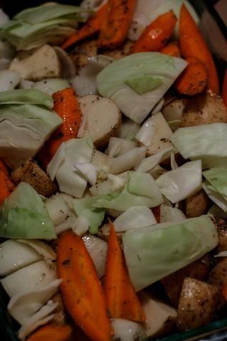 Cortar las zanahorias, las papas, la cebolla restante y el repollo en trozos grandes. Escudo con aceite de oliva y sazonar con las hierbas y especias. Coloque esto en el horno con la carne de cerdo.