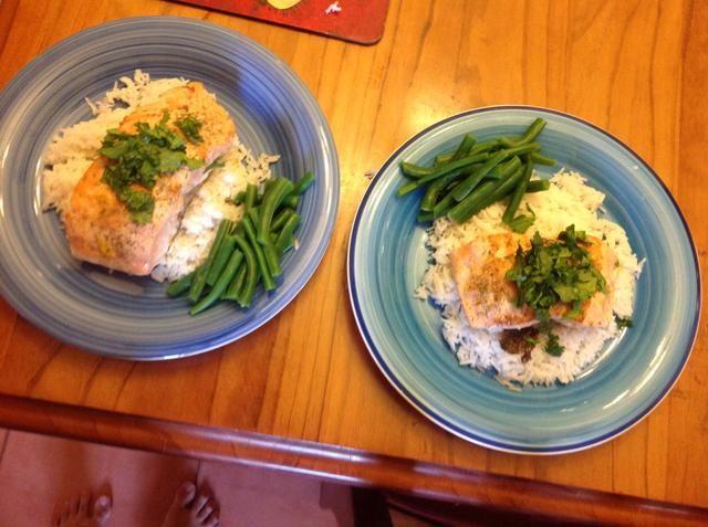 Servir el arroz, salmón y frijoles. Adorne con cilantro.