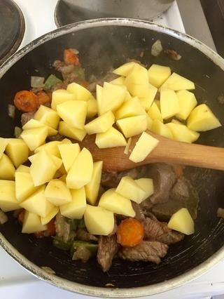 Cuando la carne es de color marrón añadir las patatas y revuelva un poco