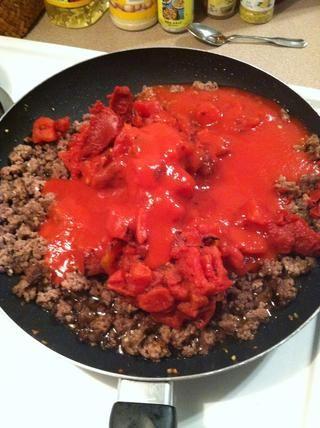 Escurrir la carne y añadir todas tus cosas de tomate. Tomates cortados en cubitos, salsa de tomate y pasta de tomate. Revuelva muy bien, llevar a ebullición a continuación, cubrir y dejar cocer a fuego lento durante unos minutos para espesar.