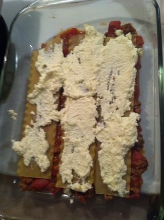 Poner un poco de la mezcla de queso sobre los fideos. Usted tendrá tres capas de la extensión de queso.