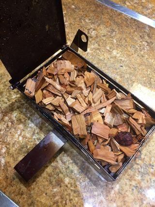 Coloque astillas de madera empapadas en el cuadro de fumador y adjuntar al horno.