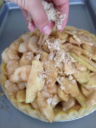Espolvorear la parte superior de migas en la parte superior de las manzanas