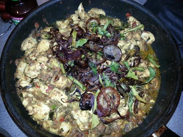 Arriba el Malabar pollo al curry con la cebolla frita. Disfrute de este con un reconfortante servir de Ghee Rice.