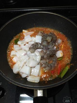 Una vez que la salsa es perfecta para su gusto (puede ser un poco más fuerte que la salsa se diluirá levemente después de gambas y calamares agregados), añadir tanto los langostinos y calamares en.