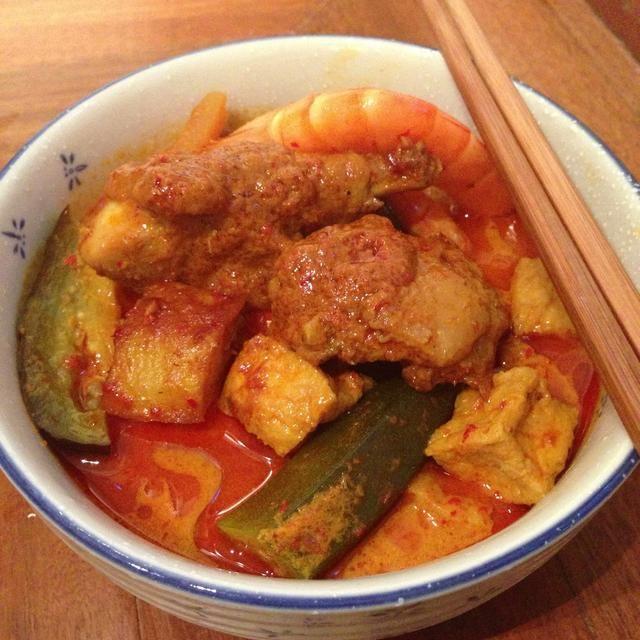 Coloque los fideos cocidos en un tazón y cuchara de la sopa con verduras en. Me gusta tener el curry de pollo y gambas peladas como complementos. Servir inmediatamente.