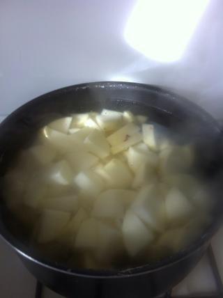 En otra olla mediana, llevar agua con una cucharada de sal kosher a hervir, añadir las patatas, hervir hasta que estén blandas (unos 10-12 minutos)