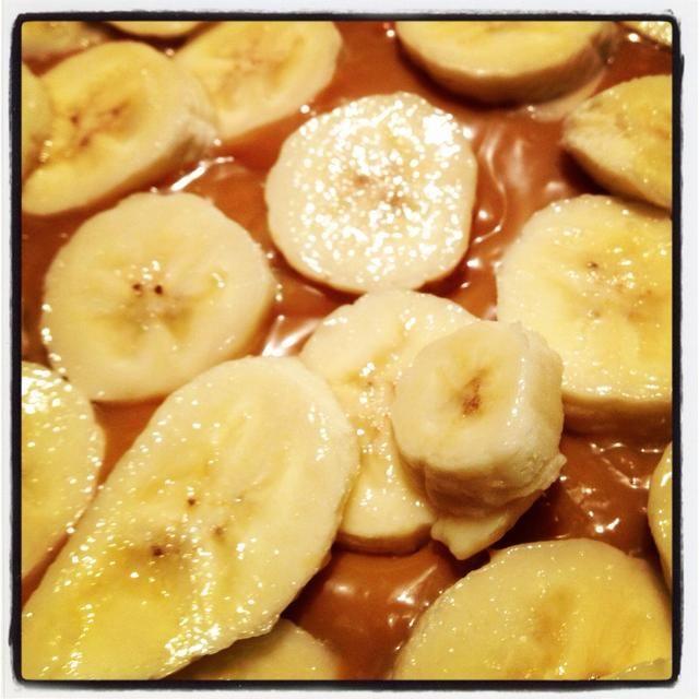 Vierta la mezcla de caramelo enfriado en la base de la galleta y cubrir con rodajas de plátano