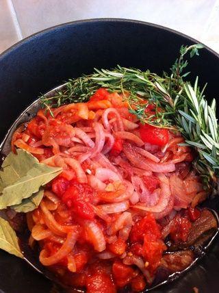 Agregue la cebolla de nuevo a la olla con la carne, añadir el vino rojo, tomates cortados en cubitos, las hierbas, y asegúrese de que el líquido apenas cubre la carne, si no añadir más agua o caldo de carne, sazonar con sal y pimienta.