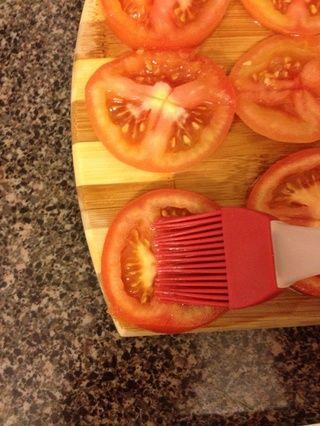 Cortar los tomates grueso, poner completamente, y difundir el aceite de oliva sobre ellos.