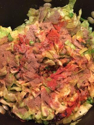 A medida que el repollo se inicia con el agua y reducir el tamaño, añadir la pimienta de cayena, comino y cilantro molido. Mantenga la mezcla para evitar la col de ennegrecimiento.