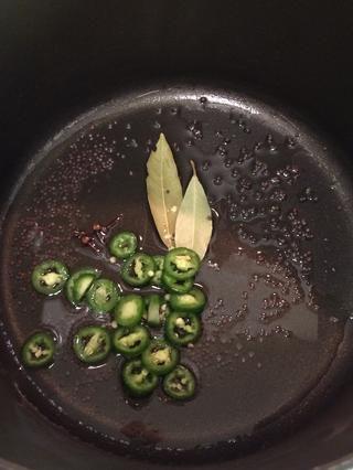 En una olla a fuego medio, agregar el aceite. En unos 1-2 minutos. agregar la semillas de mostaza, clavo, hojas de laurel y la pimienta serrano negro.
