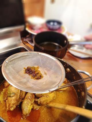 Cuando el curry está hirviendo, colar la semilla de aceite y achiote en el bote. Apague el fuego.