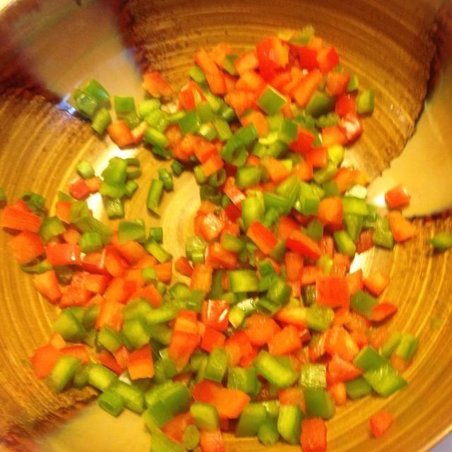 Picar los pimientos y la cebolla verde.