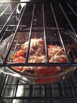 Coloque bocadillos de berenjena en una fuente para horno y verter la salsa marinara terminado. Espolvorear con queso parmesano sobrante. Hornear durante 30 minutos aproximadamente.