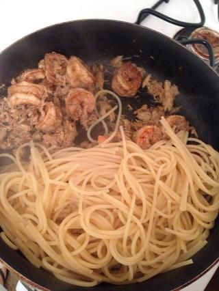 Añadir los espaguetis a la sartén para que pueda absorber los sabores de los camarones y cangrejos.