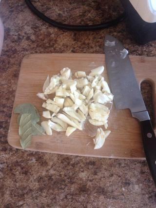 Alrededor de cortar y aplastar todo un lío de ajo. Añadir dos hojas de laurel.