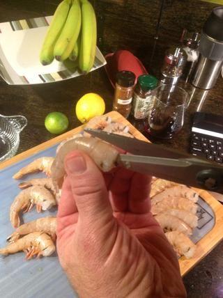 Usando tijeras de cocina cortar camarones abierta desde el centro hacia la parte posterior de la cola y desvenar.