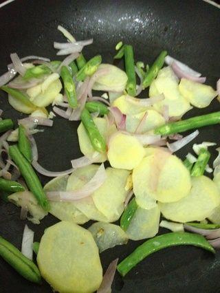 Añadir un poco de mantequilla a fuego medio y sofría la cebolla, patatas y judías verdes hasta que estén doradas. .