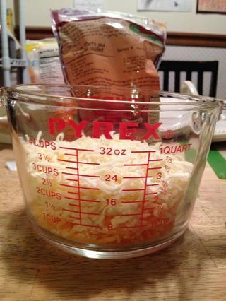 Mida el queso y mezclar juntos. Agregue la mitad de los macarrones y carne guardar el resto para la parte superior.