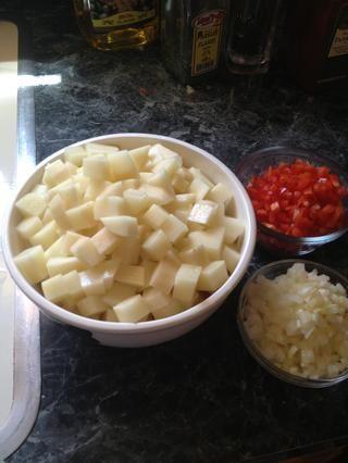 Picar las patatas. Picar las cebollas y los pimientos reservados.
