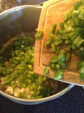 Agregar la cebolla, el apio y pimiento verde a la grasa de tocino y cocinar hasta que estén tiernos.
