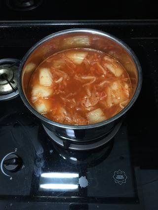 Añadir 3 tazas de agua y llevar a hervir en fuego medio durante unos 10 minutos hasta que se ablanden kimchi.