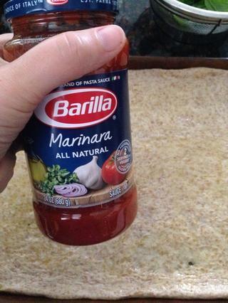 El uso de cualquier salsa marinara, cucharada 4 cucharadas colmada pena y extender uniformemente sobre la masa.