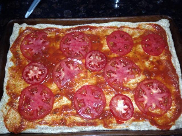Coloque las rodajas de tomate para cubrir la masa.