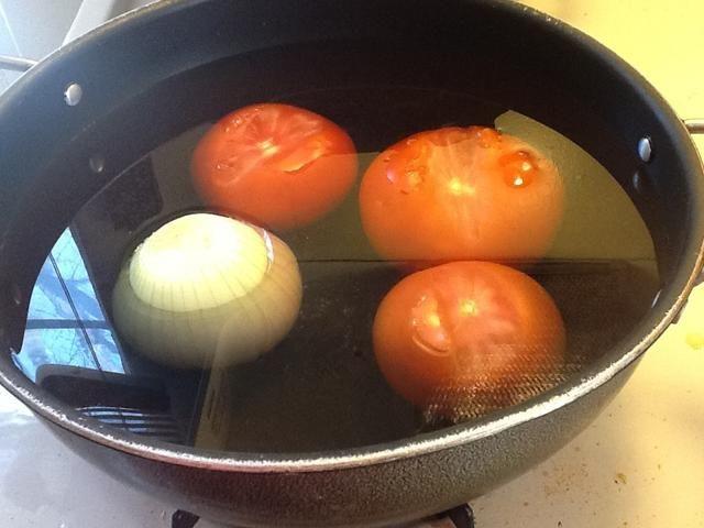 En un recipiente de agua hierva, añadir los tomates y la cebolla y se deja hervir durante unos 10 minutos
