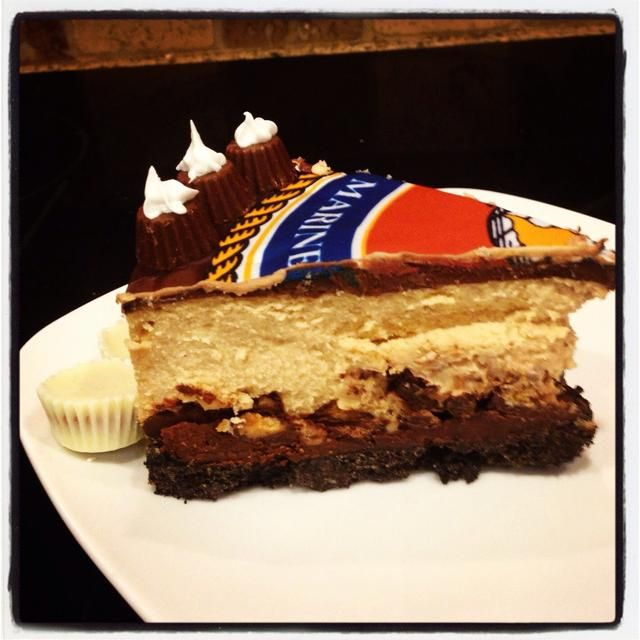 Rebanado para mostrar capas. Corteza Oreo, chocolate derretido, Reese picada's cups, peanut butter cheesecake, melted chocolate.