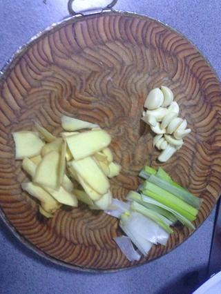 cuando el azúcar se convierta en color rojo oscuro, ponga hervida de cerdo, la cebolla, el jengibre y el ajo en una sartén.