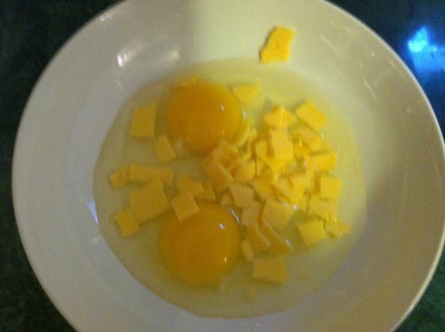 Romper el queso en trozos pequeños para que se derriten más rápido y se mezcla en los huevos durante la cocción (yo usé una rebanada para mis 2 huevos)