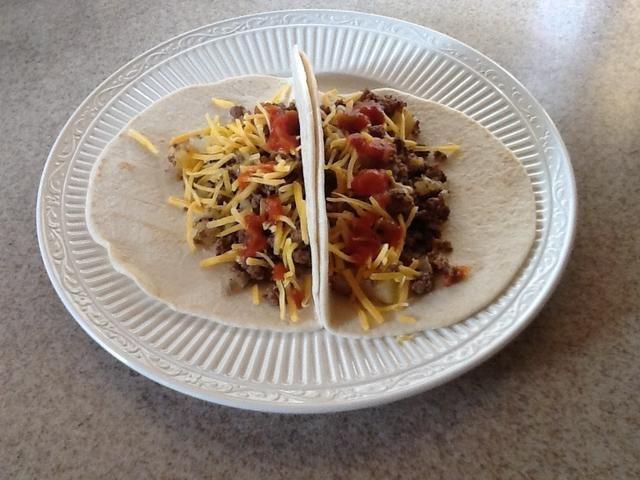 El producto terminado. En la tortilla, poner una cucharada grande de la mezcla de carne, cebolla y patatas, a continuación, añadir un poco de queso y salsa.