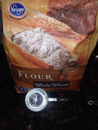 Ahora añadiendo uno a la vez, el 3 cucharadas de harina para todo uso (I utiliza trigo) a la masa a la vez mezclador todavía está mezclando a velocidad baja.