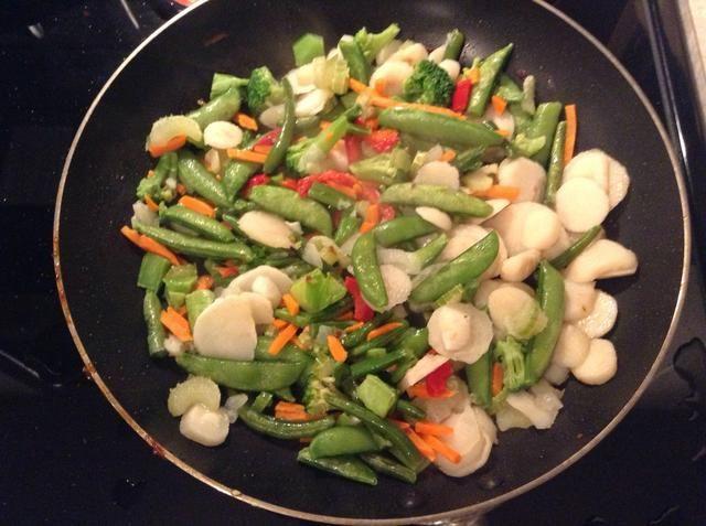 Agregue vegetales salteados, la mitad de aceite de semilla de sésamo, y el caldo de pollo a la sartén.