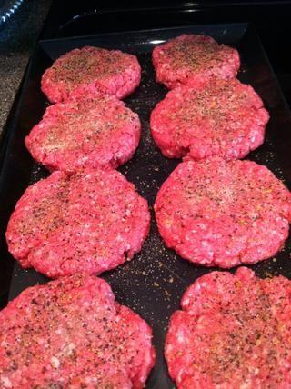 Temporada de la parte superior e inferior de cada hamburguesa con Montreal sazonar carne y ajo en polvo.