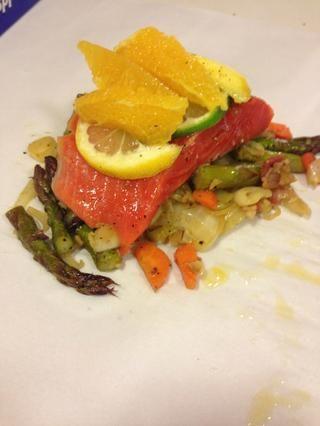 Ahora coloque un pedazo grande de papel de pergamino (asegúrese de que no la cera, la cera se quema) añadir algunas de las verduras, el salmón, rociar con aceite de oliva, agregar limón y de la cal y segmentos continuación naranja